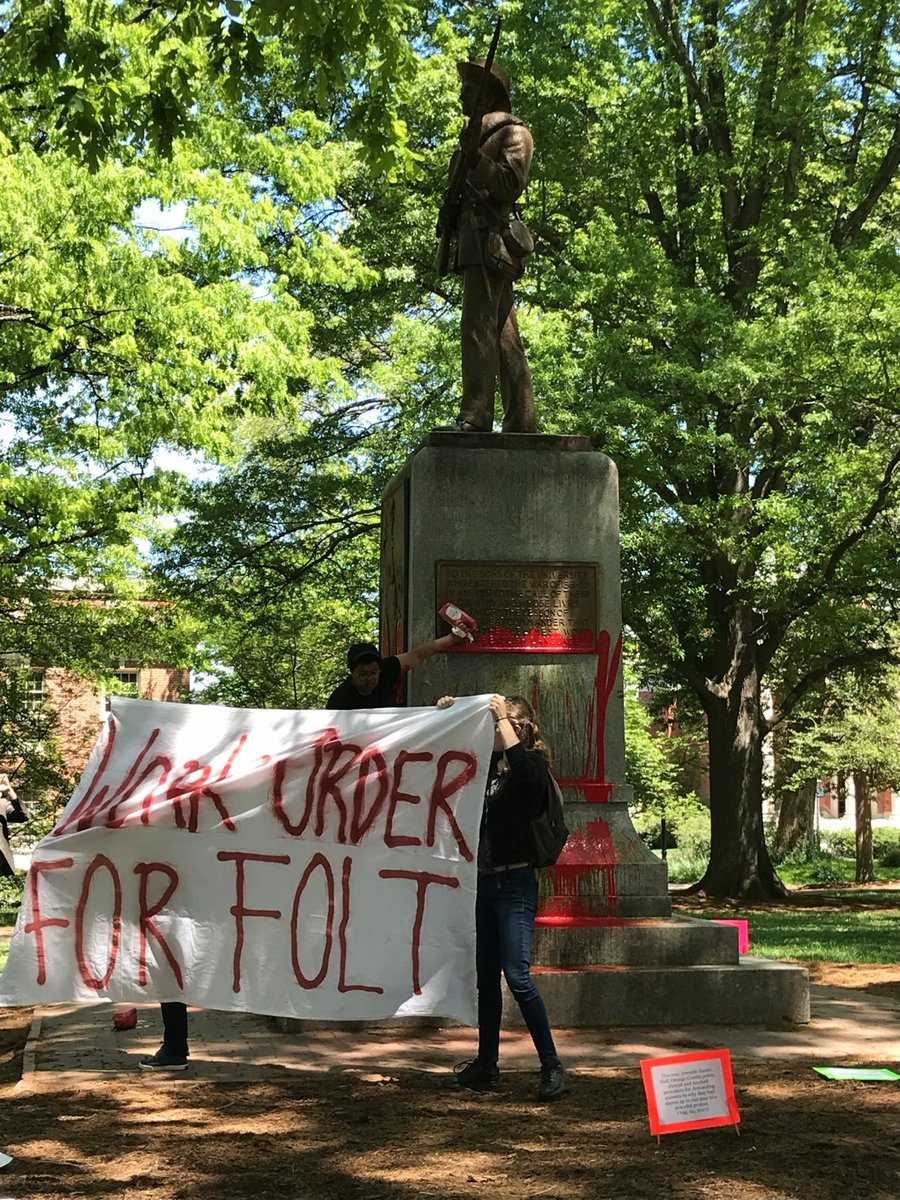 "Students hold a sign that read ""WORK ORDER FOR FOLT"" while Maya Little pours ink and blood on Silent Sam (Image by permission of the Workers Union at UNC-CH)."