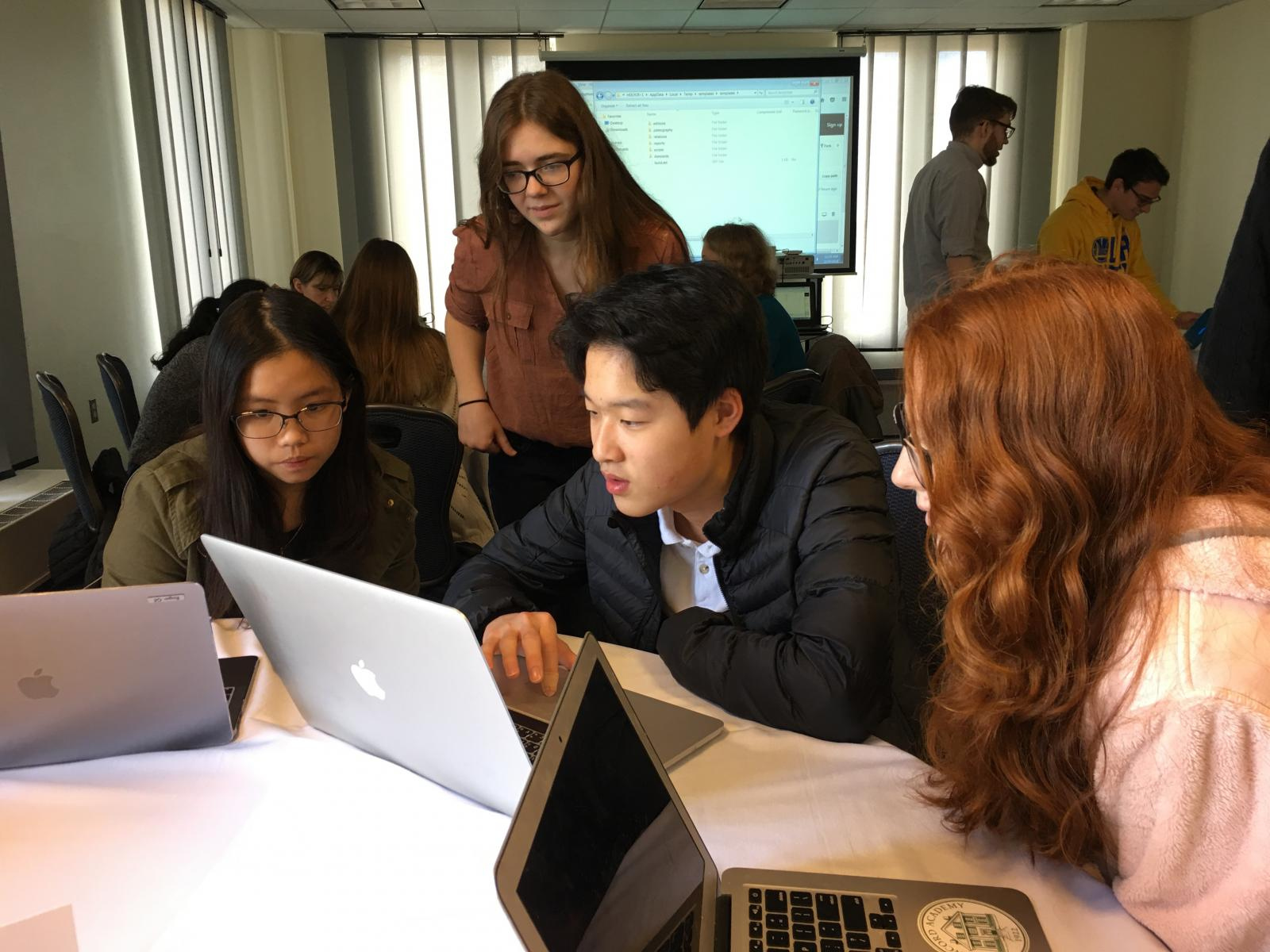 Concord Academy freshmen Cherie Jiraphanphong and Roger Ge work with CA junior Katie Painter and Holy Cross student Sophia Sarro to markup a section of the Bern Paleologus manuscript. Photo credit: Liz Penland