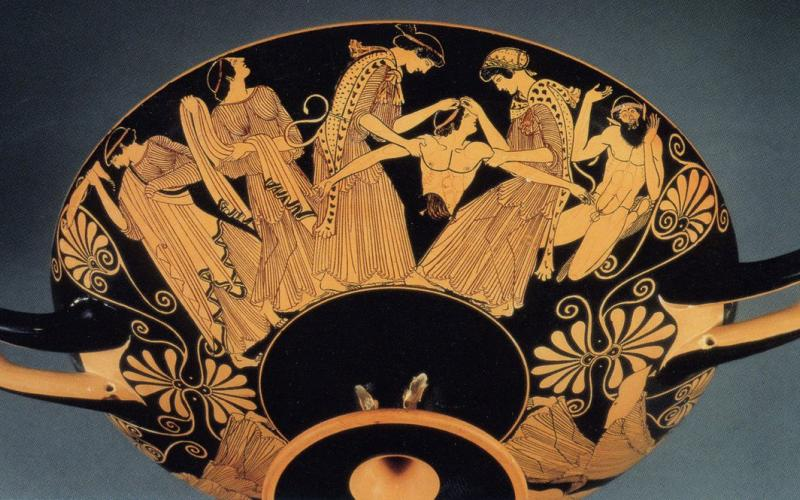 A Greek red-figure cup depicting the disembodied torso of a man, arms outstretched, and women on either side holding the torso