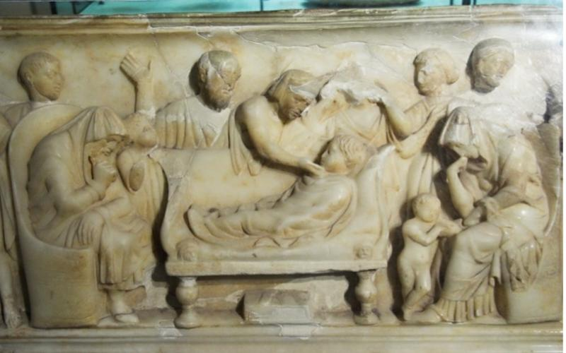 Stone relief in which the body of a child lies on a couch, surrounded by people in various gestures of mourning.