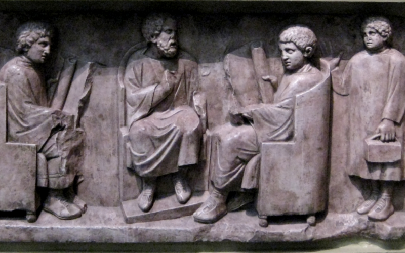 Relief found in Neumagen near Trier, a teacher with three discipuli (180-185 AD). Photo courtesy of Wikimedia commons.