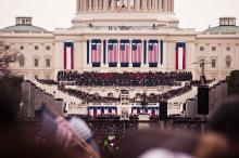 57th Presidential Inauguration, 21 January 2013. View of the U.S. Capitol building from the crowd, with people waving flags.