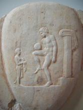 Ancient Greek football player balancing the ball. Part of a marble grave stele, found in Piraeus, 400-375 BC. Item (NAMA) 873 of the National Archaeological Museum, Athens. Image via Wikimedia under Public Domain.