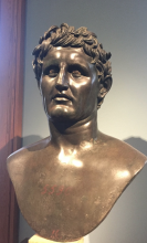 A bronze bust of a man with short, wavy hair and a slightly pained expression on his face.