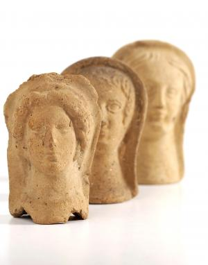 Three Roman votive offering representing faces. Credit: Wellcome Collection. CC BY 4.0: https://wellcomecollection.org/works/vy2engnk