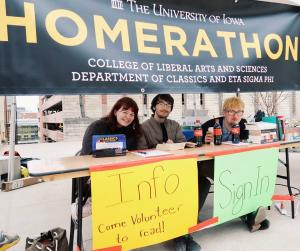 Eta Sigma Phi students, Callie Todhunter, Noah Andrys, and Myles Young, staff the Homerathon booth at the University of Iowa