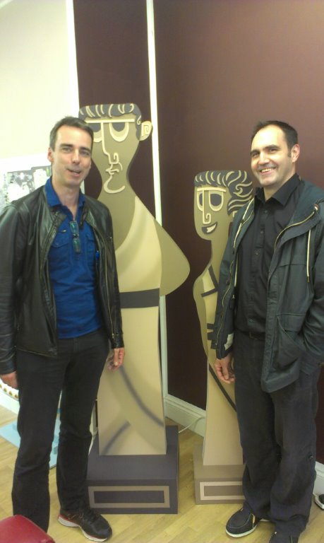 Figure 1: Ray Laurence and Andrew Park pose next to cut-outs of animated characters drawn for their TedEx series.